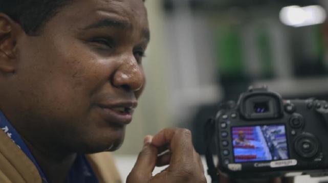 Foto do rosto de João maia de lado atrás da câmera canon