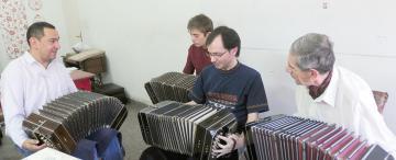 Un maestro que enseña a hacer música con viento entre cuatro paredes