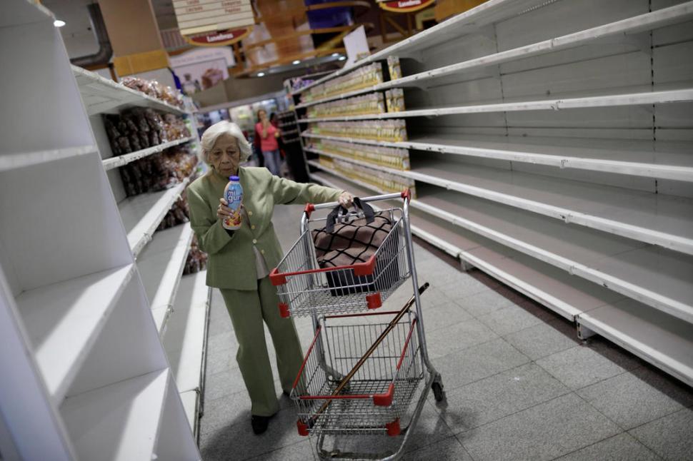APROVISIONÁNDOSE. La gente compra productos básicos en un supermercado, casi vacío, de Caracas. Reuters