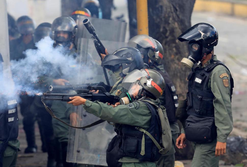 CARACAS. Integrantes de las fuerzas de seguridad antidisturbios disparan contra manifestantes que se movilizaron en contra del gobierno de Maduro. reuters