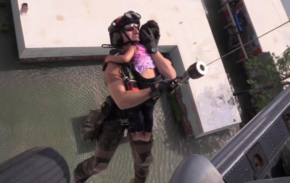 HOUSTON. Un rescatista lleva a un niño que estaba atrapado en su casa.   fotos de Reuters