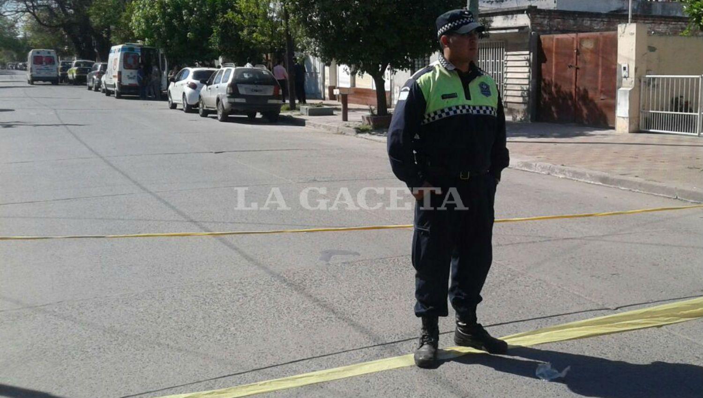 CUSTODIA. Un policía cuida la cuadra donde ocurrió el crimen. De fondo, las ambulancias. LA GACETA / FRANCO VERA