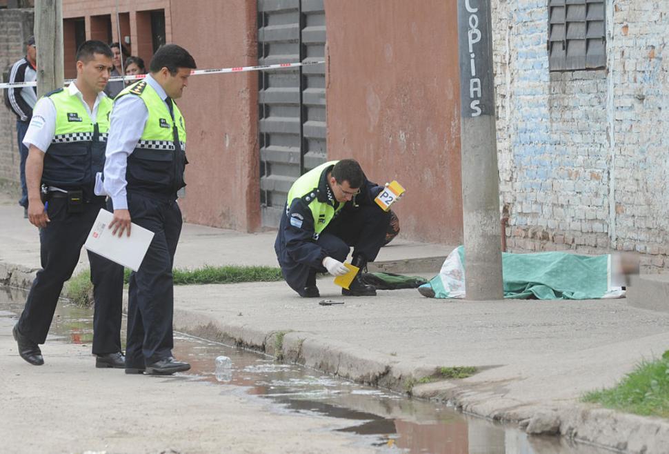 MUERTE EN LA AVENIDA SAN RAMÓN. El cuerpo del joven abatido quedó entre un poste y la pared de la fotocopiadora, cerca del revólver. la gaceta / foto de Antonio Ferroni