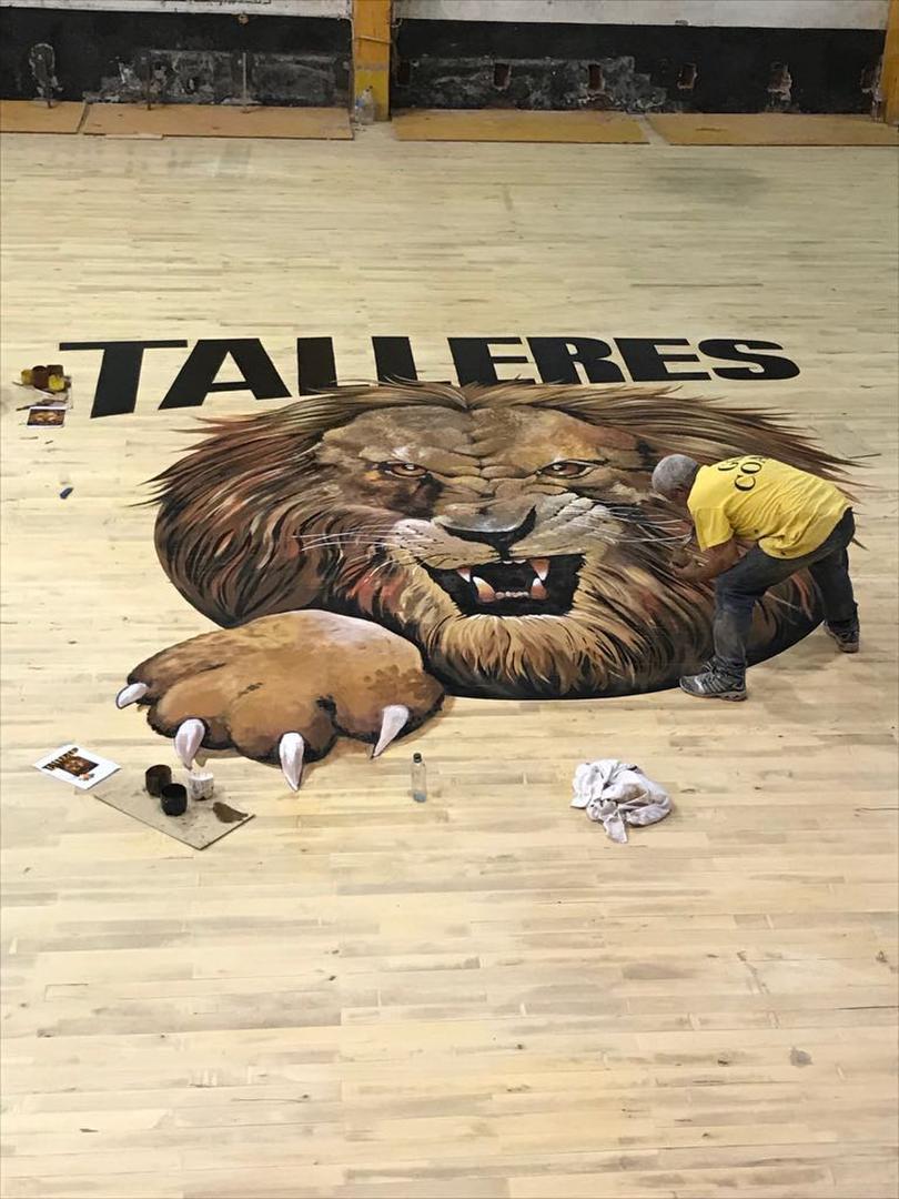 """UNA PINTURITA. El artista taficeño """"Atilio"""" termina de pintar el león -apodo de Talleres- en el centro de la renovada cancha. prensa talleres"""