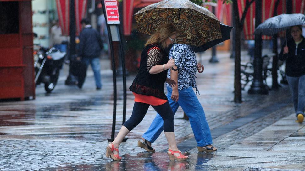 LLUVIAS FUERTES. Dos personas intentas protegerse de la lluvia en pleno centro tucumano. ARCHIVO