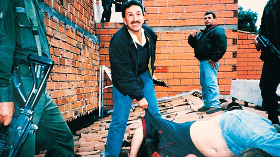 EN EL TEJADO. Hugo Aguilar junto al cuerpo sin vida de Pablo Escobar. FOTO ARCHIVO