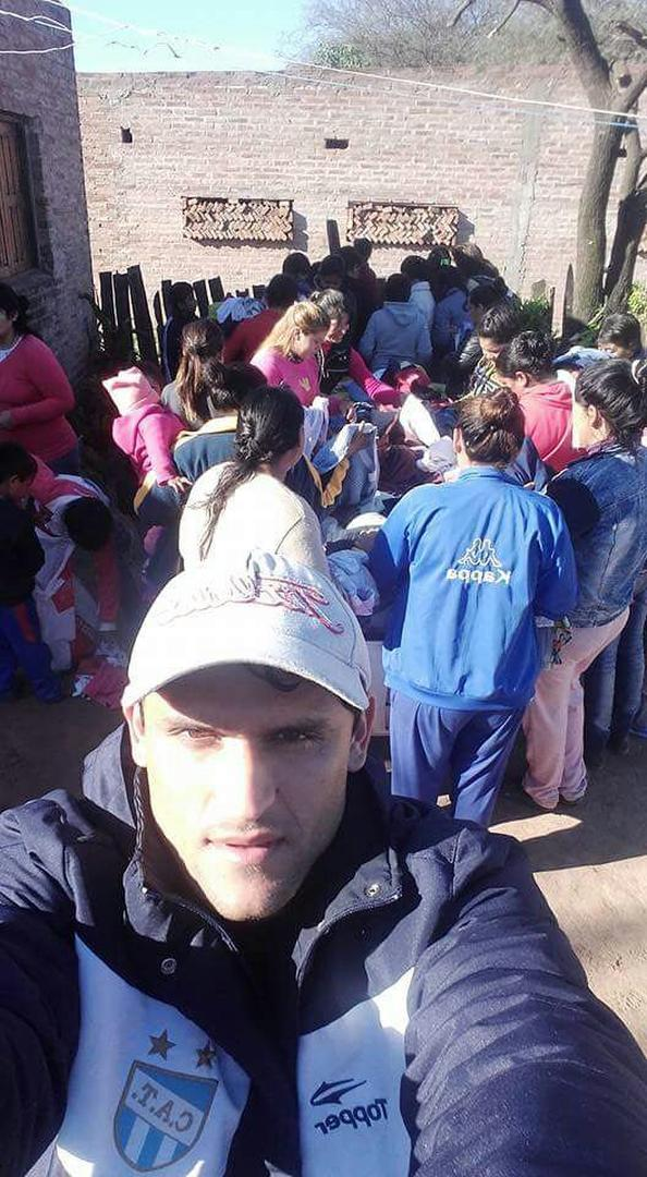 SELFIE. En primer plano, Montiglio; detrás, los pobladores de la localidad chaqueña de Taco Pozo distribuyen las donaciones. credito xxxxxxxx