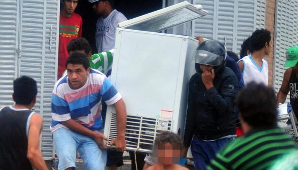 EL CAOS SE APODERABA DE LAS CALLES. Dos personas fueron retratadas mientras se apoderaban de una heladera de gran tamaño que robaron de un local comercial.